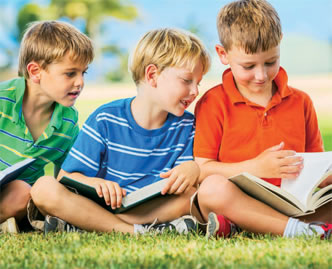 three young boys reading outside